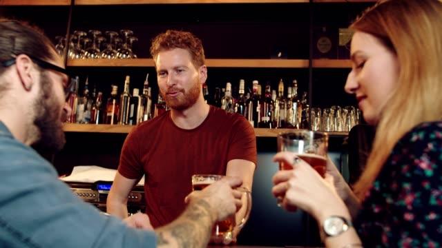 바텐더와 이야기하는 친구들. - bartender 스톡 비디오 및 b-롤 화면