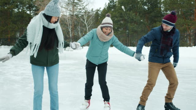 friends teaching young woman to ice-skate in winter park but amateur falling and laughing - lega sportiva amatoriale video stock e b–roll
