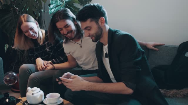 friends texting with cell phone in cafe - młodzi mężczyźni filmów i materiałów b-roll