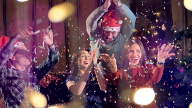 Friends throw confetti in the air at Christmas time. video