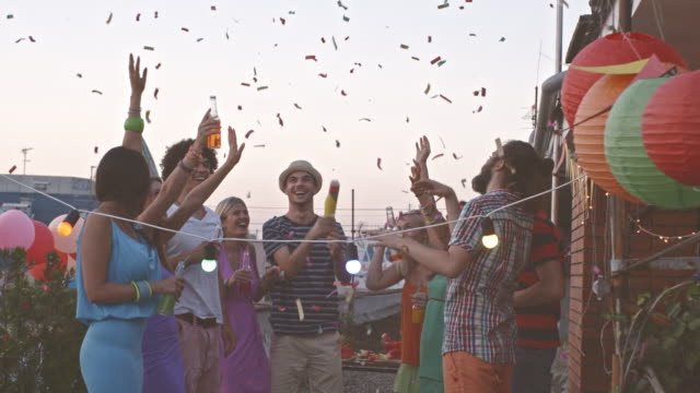 Friends throwing confetti at rooftop party video