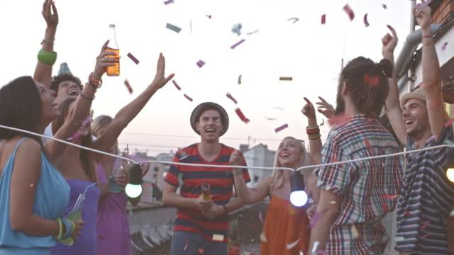 Amigos tirando confeti en fiesta en la azotea - vídeo