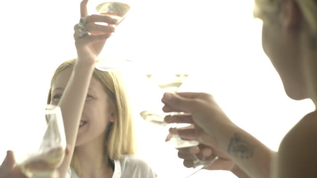 Friends toast and drink white wine at italian restaurant CU video