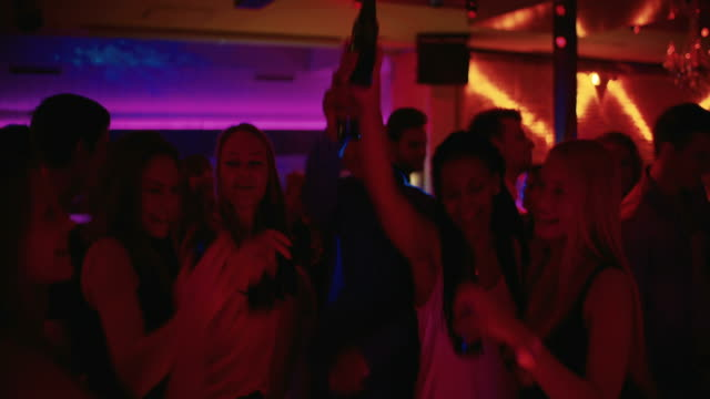 Friends toasting and holding beer high at a party on dance floor video