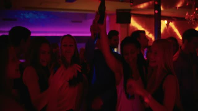 Amigos brindis alta retención y cerveza en un partido en una pista de baile - vídeo