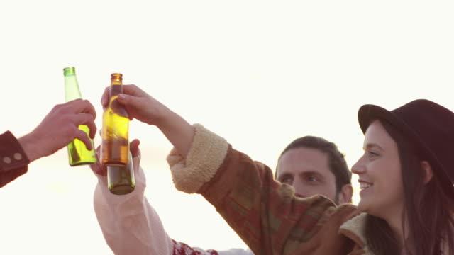 friends toasting beer bottles on terrace in summer - terrazza video stock e b–roll