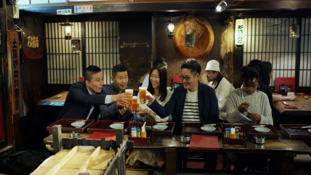 Friends Toasting Beers in Busy Tokyo Restaurant A busy evening at a robata restaurant in Tokyo, Japan. celebratory toast stock videos & royalty-free footage