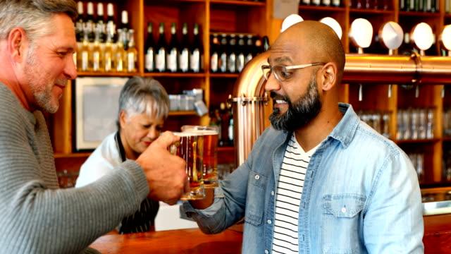 friends toasting glass of beer at counter in restaurant 4k - 40 49 lat filmów i materiałów b-roll