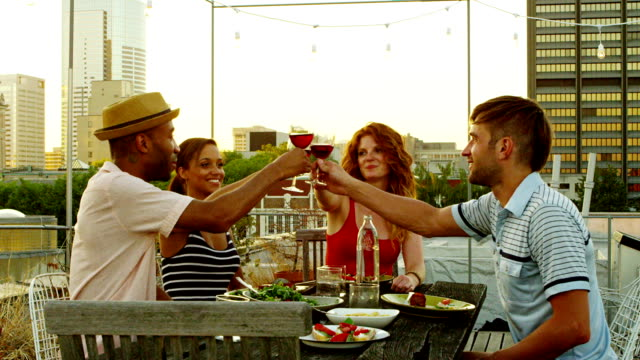 Friends toasting wine glasses dining at table on rooftop video