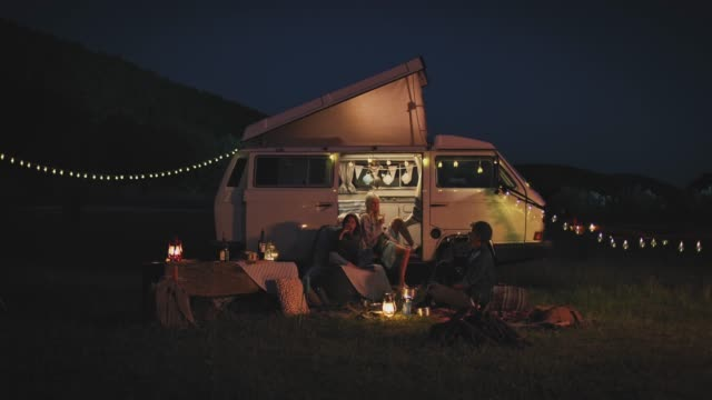 Friends toasting wineglasses while camping at night