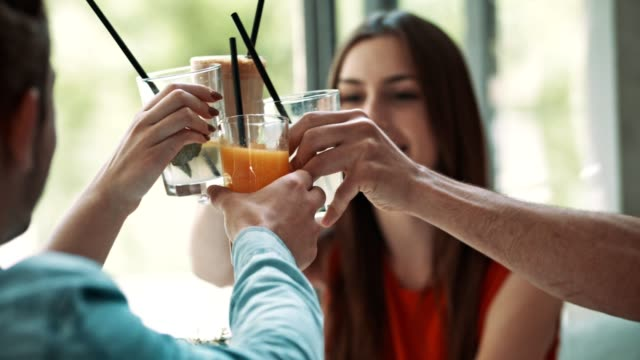 vídeos y material grabado en eventos de stock de amigos brindando con bebidas en la cafetería - zumo