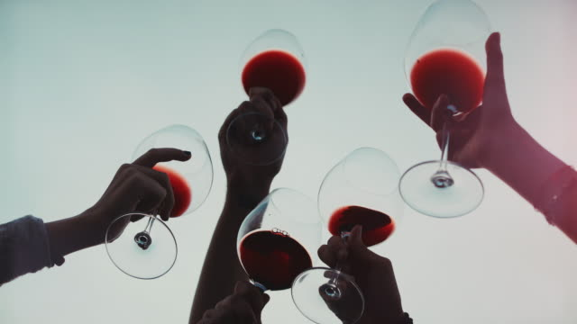 Friends together enjoy red wine: up the glasses