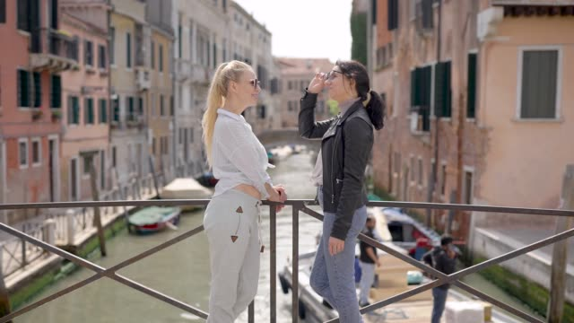 friends travel around venice. the famous city in italy attracts with its streets and cafes, as well as the ancient architecture - young couple wedding friends video stock e b–roll