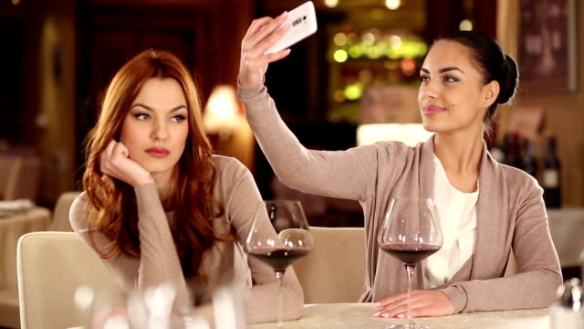 Friends using their smart phones at the restaurant video
