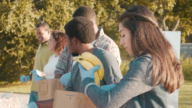 Friends volunteer together at outdoor food drive during coronavirus pandemic A young woman volunteers during an outdoor food drive with her friends. The volunteers are packing paper bags with food donations. They are giving the donations to people impacted by the COVID-19 crisis. giving tuesday stock videos & royalty-free footage