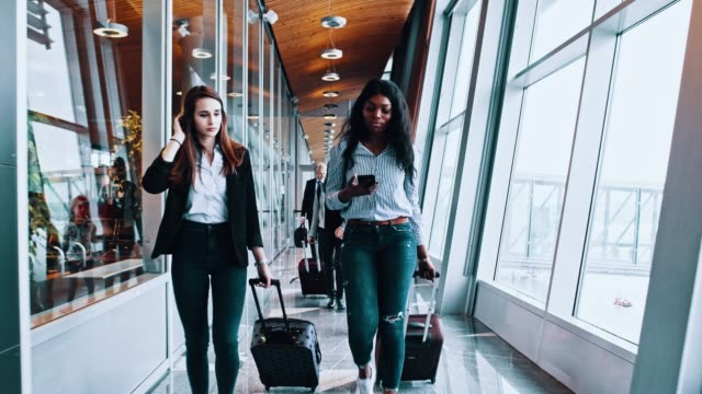 friends walking and pulling suitcases along the window at the airport - two students together asian video stock e b–roll