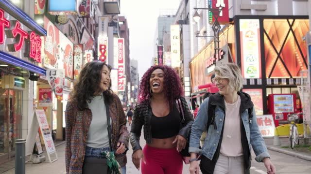 vidéos et rushes de amis marchant sur une rue à tokyo - d'ascendance européenne