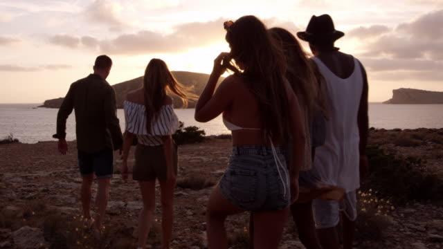 vídeos de stock e filmes b-roll de friends walking on cliff watching sunset shot on r3d - ibiza