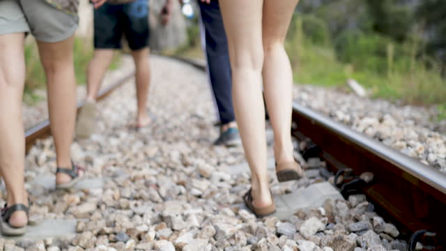 Friends walking on railroad track in nature