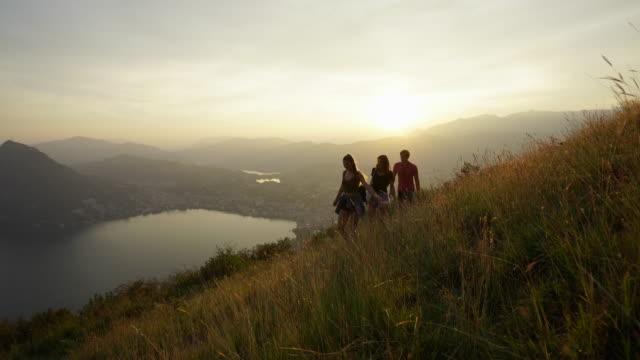 vídeos de stock, filmes e b-roll de amigos, andar pela grama alta no pôr do sol com vista para lago e cidade abaixo - camiseta preta