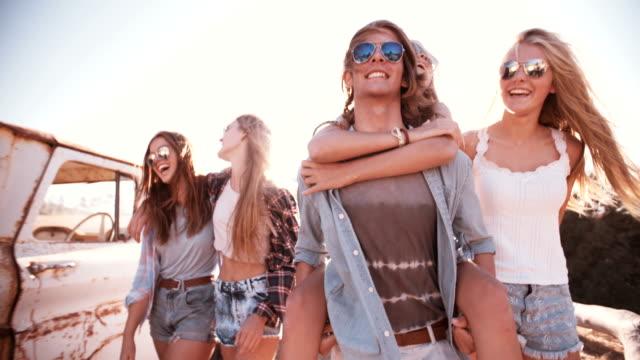 friends walking with guy piggybacking girlfriend in sun flare - solglasögon bildbanksvideor och videomaterial från bakom kulisserna