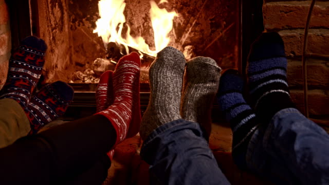 DS Friends warming their feet by the fireplace Dolly shot of a family warming their feet by the fireplace. Also available in 4K resolution. fireplace stock videos & royalty-free footage