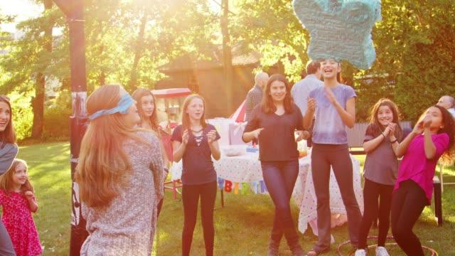 stockvideo's en b-roll-footage met vrienden kijken naar een jong meisje een piñata slaan op haar verjaardag - buren