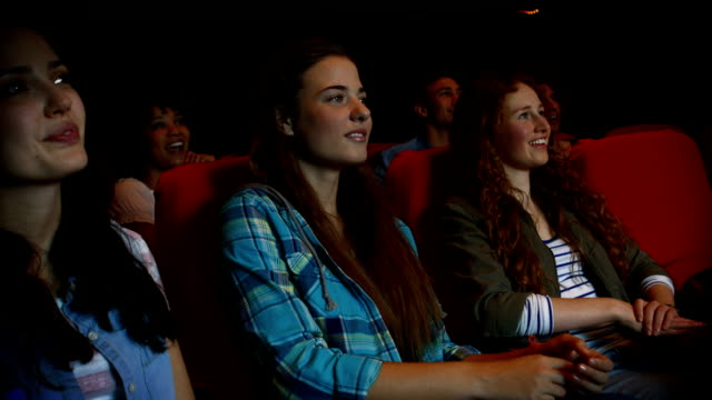 Friends watching funny movie in cinema video