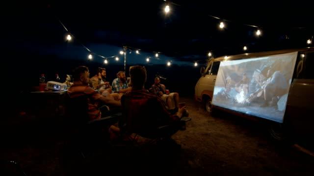amici che guardano film in campeggio - ambientazione esterna video stock e b–roll