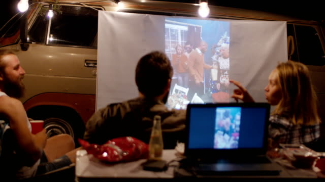 friends watching video with projector in campsite - urządzenie projekcyjne filmów i materiałów b-roll