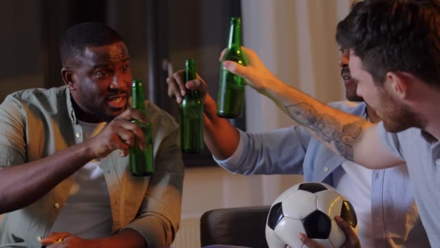 friends with ball and vuvuzela watching soccer - vídeo