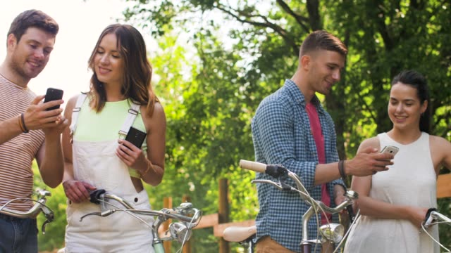 friends with bicycles and smartphones at park video