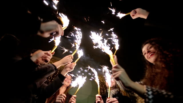 Friends with sparklers dancing. Slow motion video