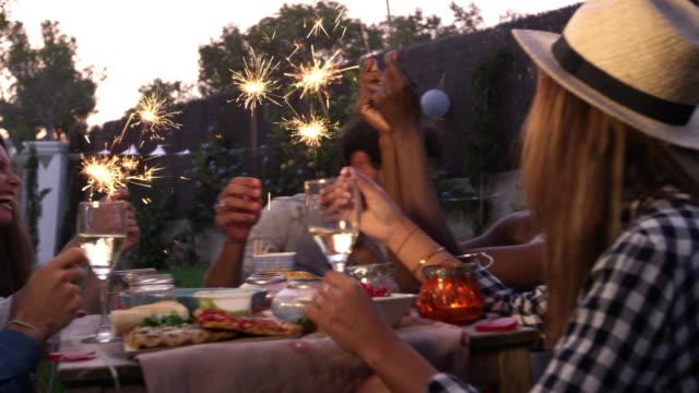 Amigos con luces de Bengala comiendo y disfrutando de la fiesta - vídeo