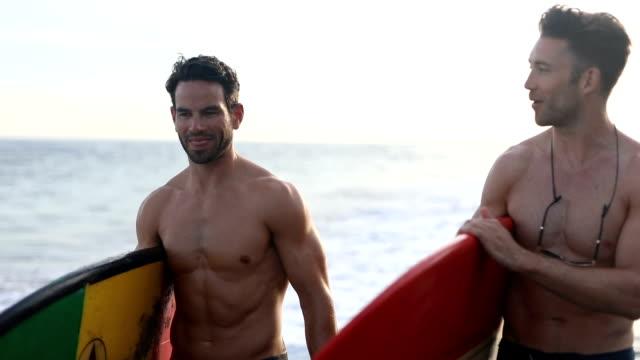 freunde mit surfbrettern am strand - nackter oberkörper stock-videos und b-roll-filmmaterial