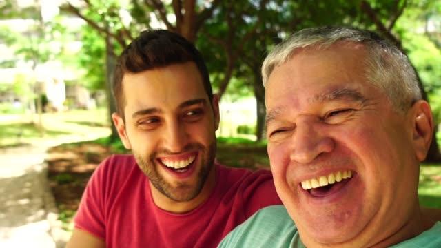 友人/父と息子の話ベンチ公園内 selfie - ブラジル文化点の映像素材/bロール