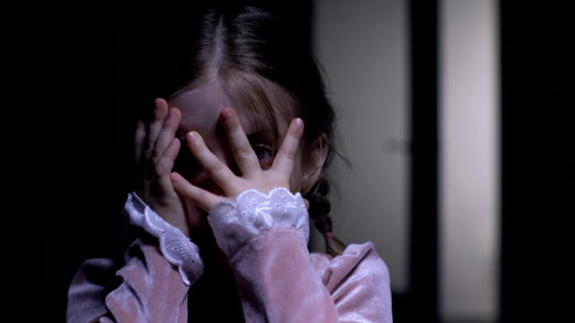 Frightened little girl closing face with palms, afraid of ghosts phobia concept