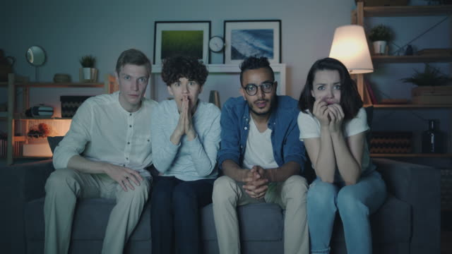 Video Frightened students watching thriller on TV with scared faces at night at home