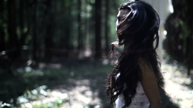 korkmuş genç kadın ormanda yürümek - fantastik stok videoları ve detay görüntü çekimi