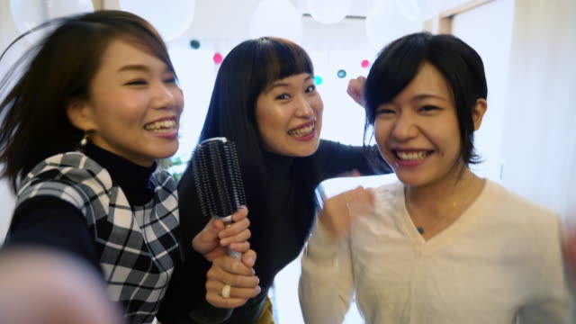 pov from a phone as three young japanese women sing karaoke at home - śpiewać filmów i materiałów b-roll