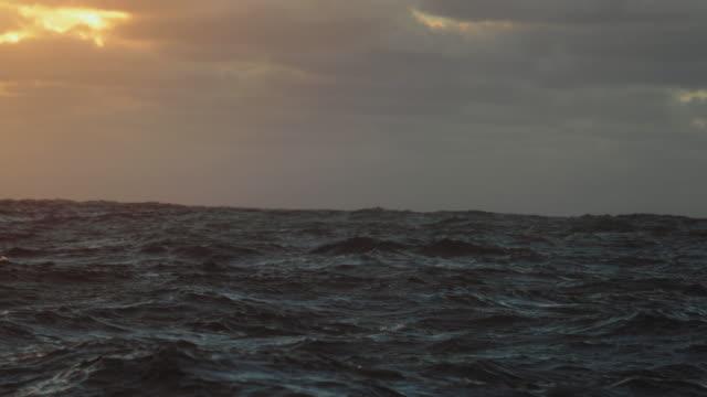aus einem segel eines schiffes: blaues meer bei sonnenuntergang - rau stock-videos und b-roll-filmmaterial