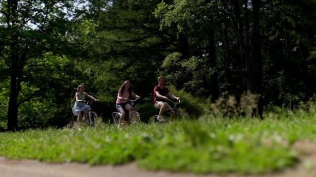 underifrån slow motion bred bild av lycklig familj av far, mor och lilla dotter njuter ridning cyklar på grönt gräs i sommarpark - naturparksområde bildbanksvideor och videomaterial från bakom kulisserna