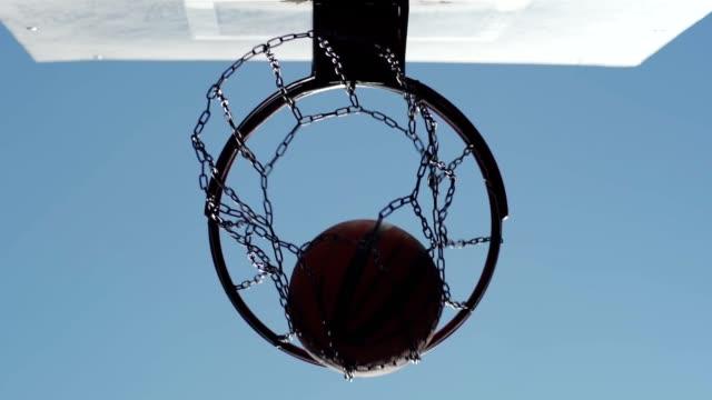 vídeos y material grabado en eventos de stock de desde abajo vista de baloncesto volando en la red de aro en cámara lenta contra el fondo del cielo azul - basketball hoop