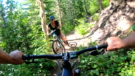 istock POV from e-bike handlebars of young women ascending trail with mountain bicycle 1256971354