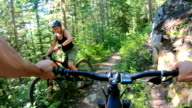 istock POV from e-bike handlebars of young women ascending trail with mountain bicycle 1256976863