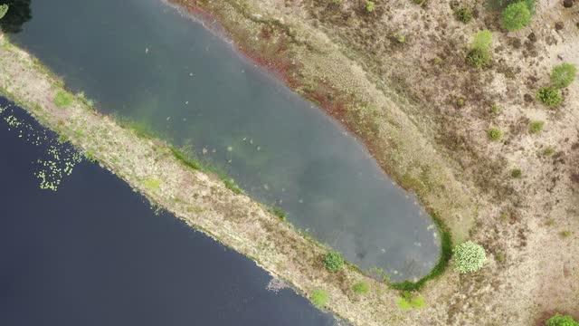pov vom flug über einen moorsee in zwei teile mit drehung über den landstreifen, luftbild - aerial view soil germany stock-videos und b-roll-filmmaterial