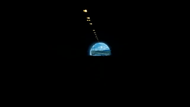 From the dark tunnel the car leaves for the road in the summer video