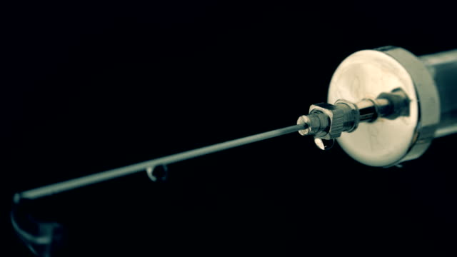 oldstyle cam şırınga iğne gelen ilaç damla akar. makro - doping stok videoları ve detay görüntü çekimi