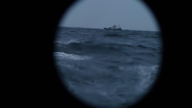 from the porthole window of a vessel in a rough sea - dziura filmów i materiałów b-roll