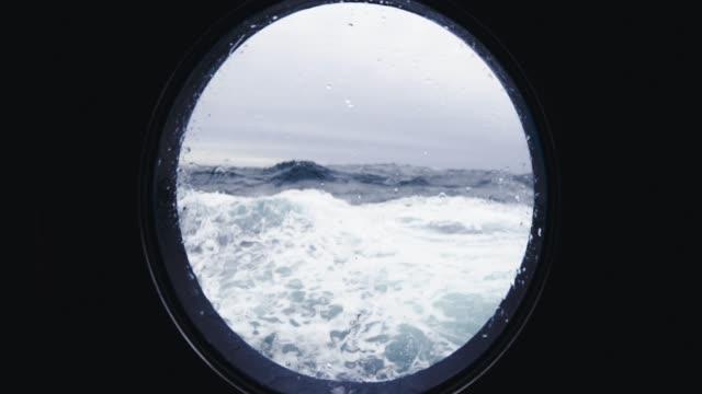 aus dem bullauge fenster eines schiffes in rauer see - rau stock-videos und b-roll-filmmaterial